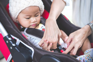 54108441 - portrait of a mother securing her baby in the car seat in her car