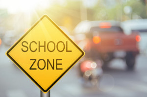 School zone warning sign on blur traffic road with colorful bokeh light abstract background.