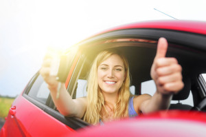 43474446 - happy woman in red car showing thumb up and key.