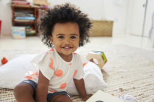 Portrait Of Happy Baby Girl Playing With Toys In Playroom