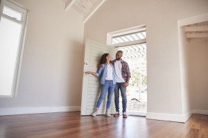 Couple Opening Door And Walking In Empty Lounge Of New Home